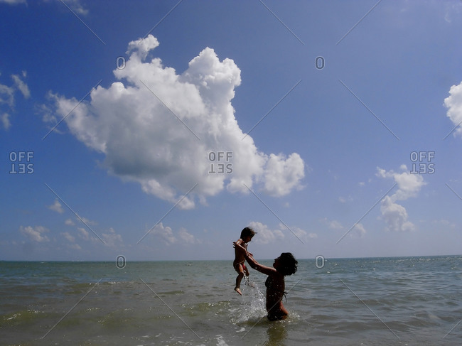 Mother and child playing in the ocean