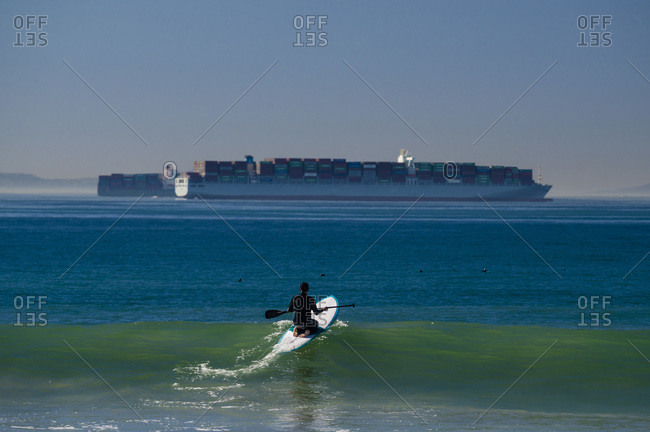 Paddle boarder riding over a wave with container ships in distance