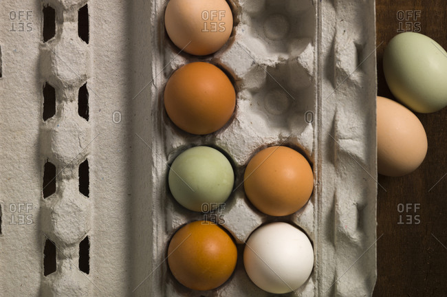 Overhead view of colorful chicken eggs in a paper carton