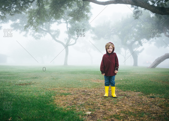 Boy standing in a foggy park with yellow boots