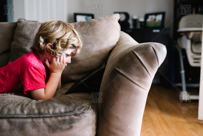 Boy reading tablet on couch