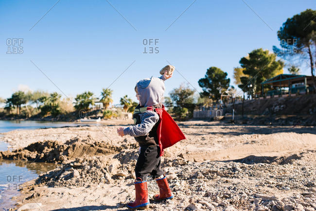 Boy throwing rock in water red cape