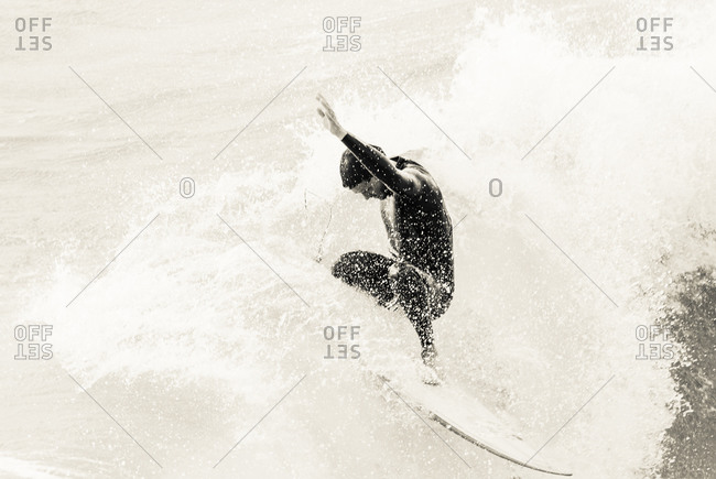 Bournemouth, Dorset, England, UK - October 5, 2008: Surfer riding a wave with his hand in the air
