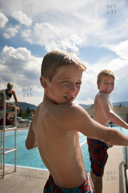 Two boys on a public pool diving board