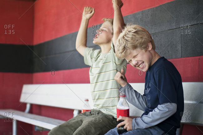 Two boys cheering on bleacher at baseball game