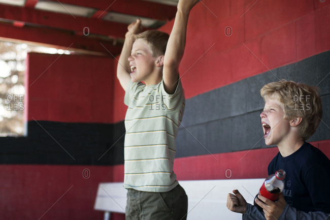 Two boys cheering on bleacher