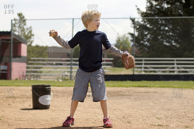 Young boy winding up to pitch baseball