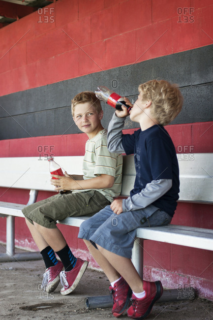 Boys drinking soda on bleacher in baseball dugout