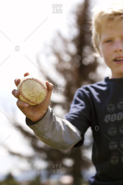 Boy holding baseball up