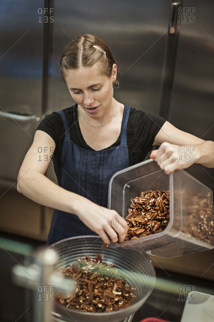 Woman in restaurant kitchen pouring out nuts