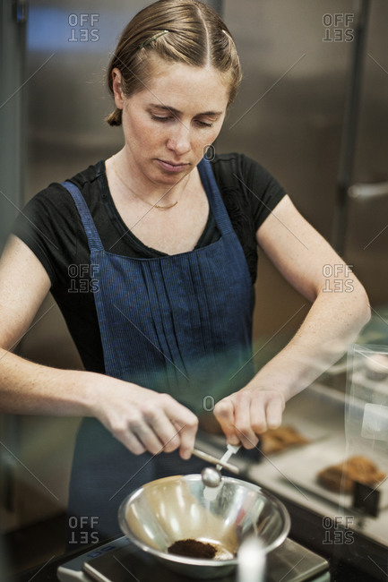 Woman in industrial kitchen measuring out dry ingredients
