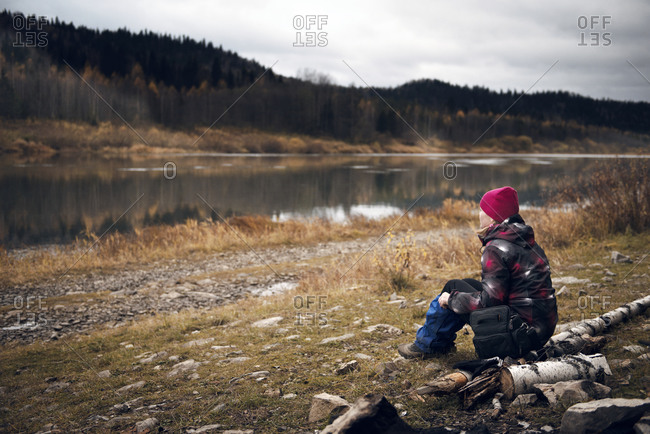 Woman sitting watching rural river in fall