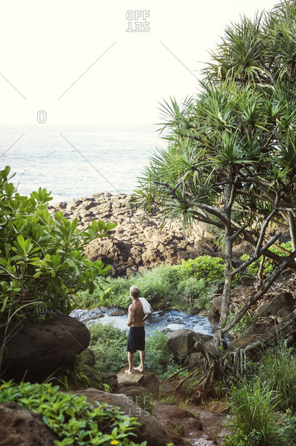 Man standing on rocky coast looking at sea