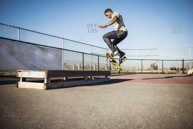 Skater jumping on a wooden block in skate park