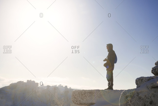 Man on ledge of mountain overlooking wilderness