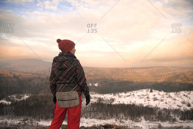 Woman standing on mountaintop overlooking wilderness