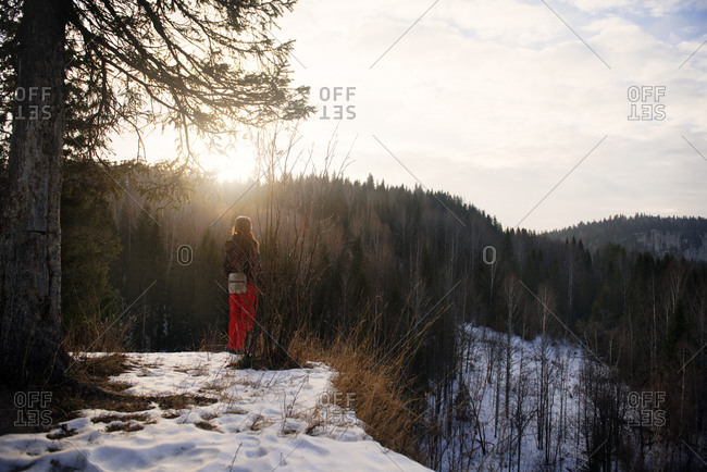 Woman on mountaintop overlooking wilderness