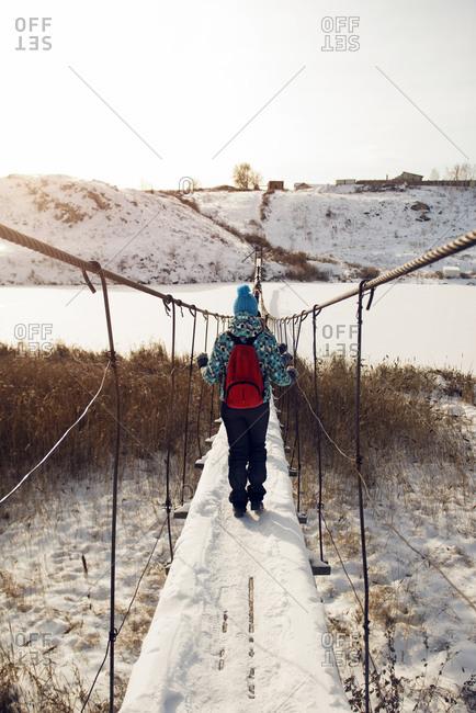 Woman crossing hanging bridge over winter river