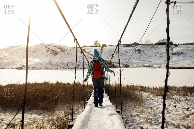 Woman crossing swinging bridge over winter river