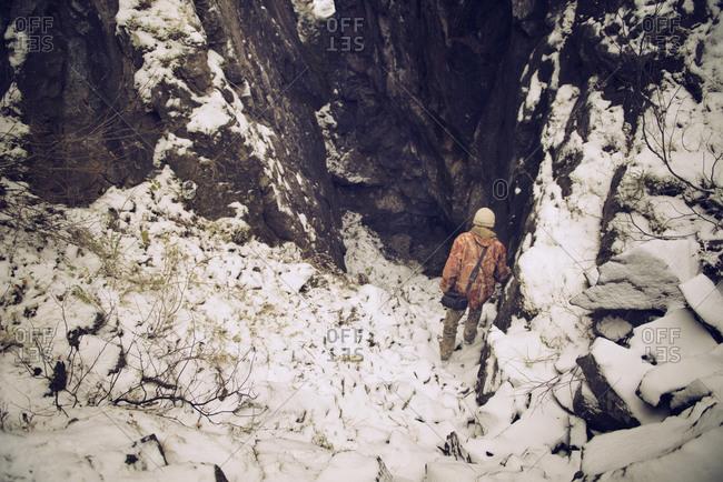 Hiker descending in rocky mountain gorge