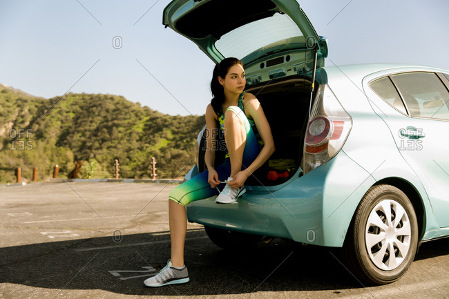 Young woman getting ready in her car