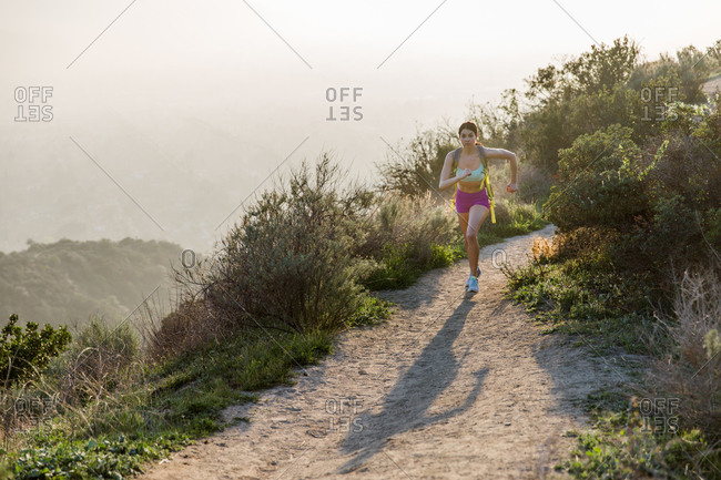Brunette woman running on a dirt road