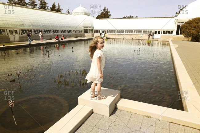 A little girl stands at the end of a pond at a conservatory