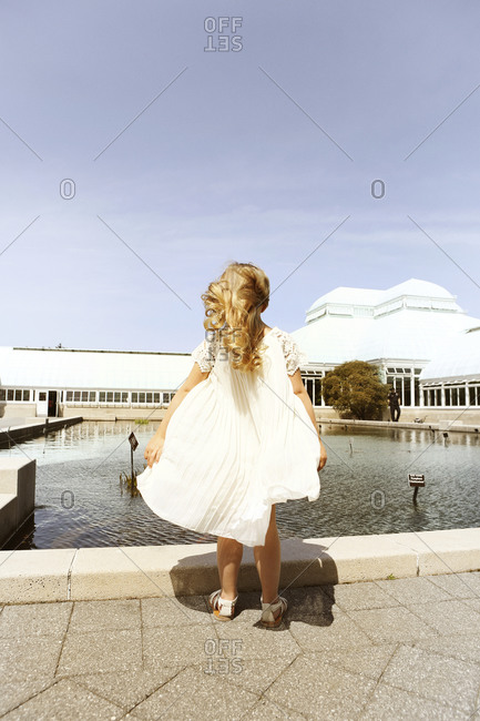 A little girl standing in the wind at a conservatory