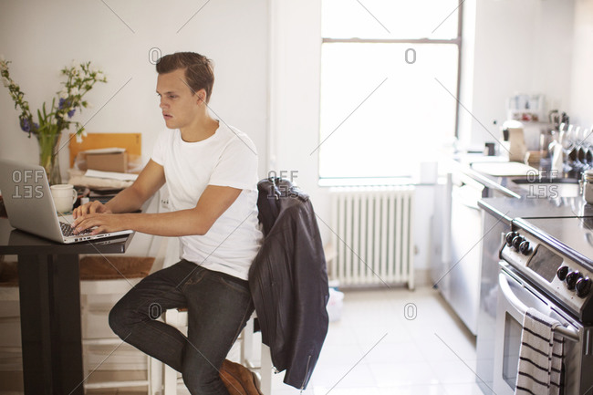 A man on a laptop at his kitchen table