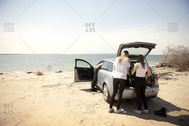 Friends unload gear from a car at the beach