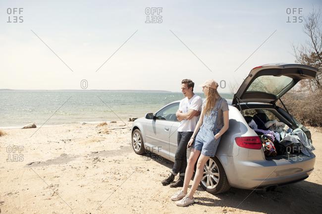 A couple lean against their car at the beach