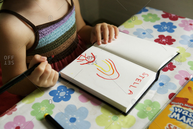 A little girl draws in a notebook