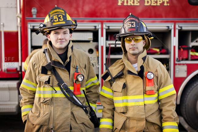 Two firefighters standing in front of a fire engine