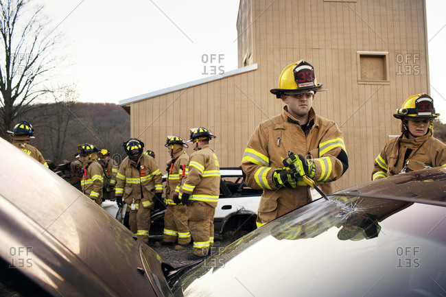 Firefighters practice breaking a windshield on a car