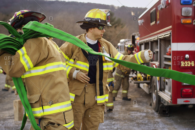 Firefighters unroll a hose from a fire truck