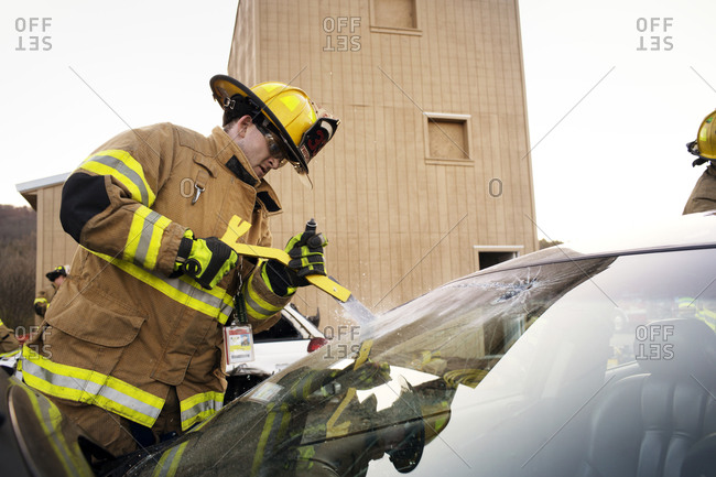 A fireman practices breaking a windshield on a car