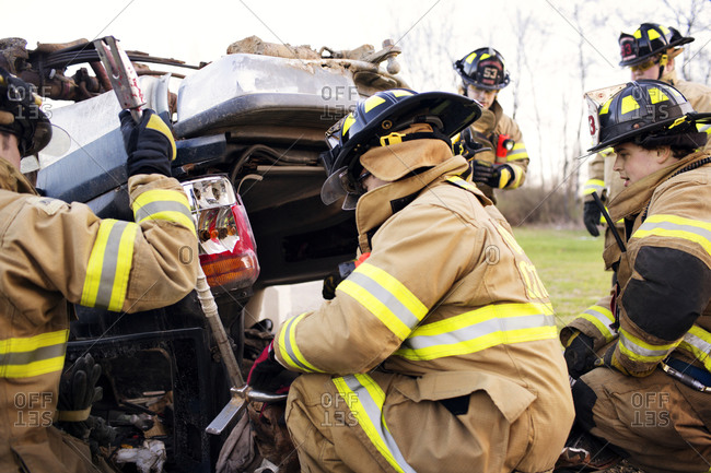 Firemen examine the wreckage of a car