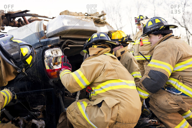 Firefighters examine the wreckage of a car