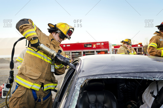 A fireman using the jaws of life to break into a car