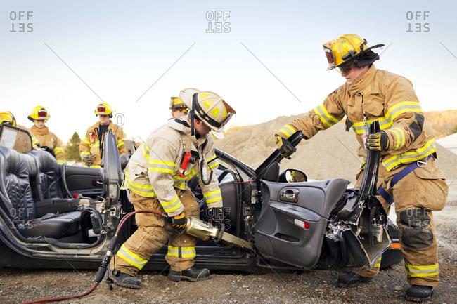 Firemen practice disassembling a car