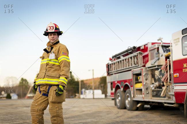 A fireman standing next to a fire engine