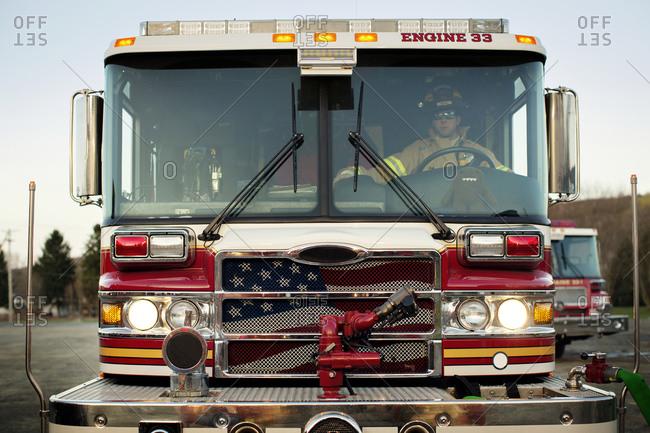 A fireman driving a fire engine