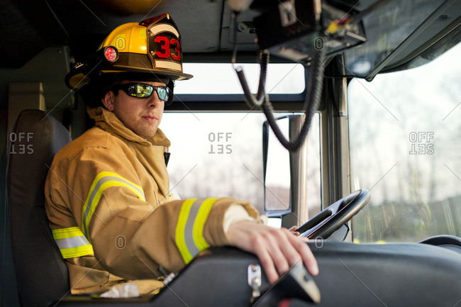 A fireman in the driver\'s seat of a fire engine