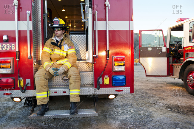 A firefighter seated in the back of a fire truck