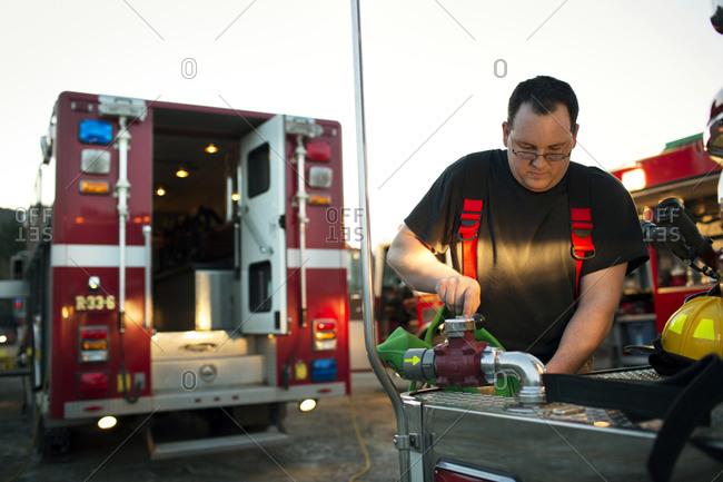A fireman checks out a fire hose on a truck