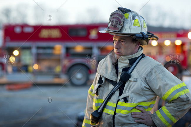 A fireman stands in front of a fire engine