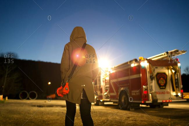 A firewoman walks towards a fire truck