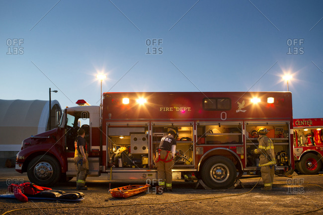 Firemen load up their fire truck at dusk