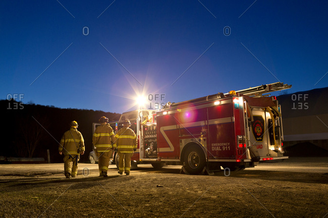 Three firefighters walking to a fire truck at night