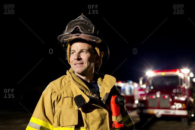 A fireman smiling at night